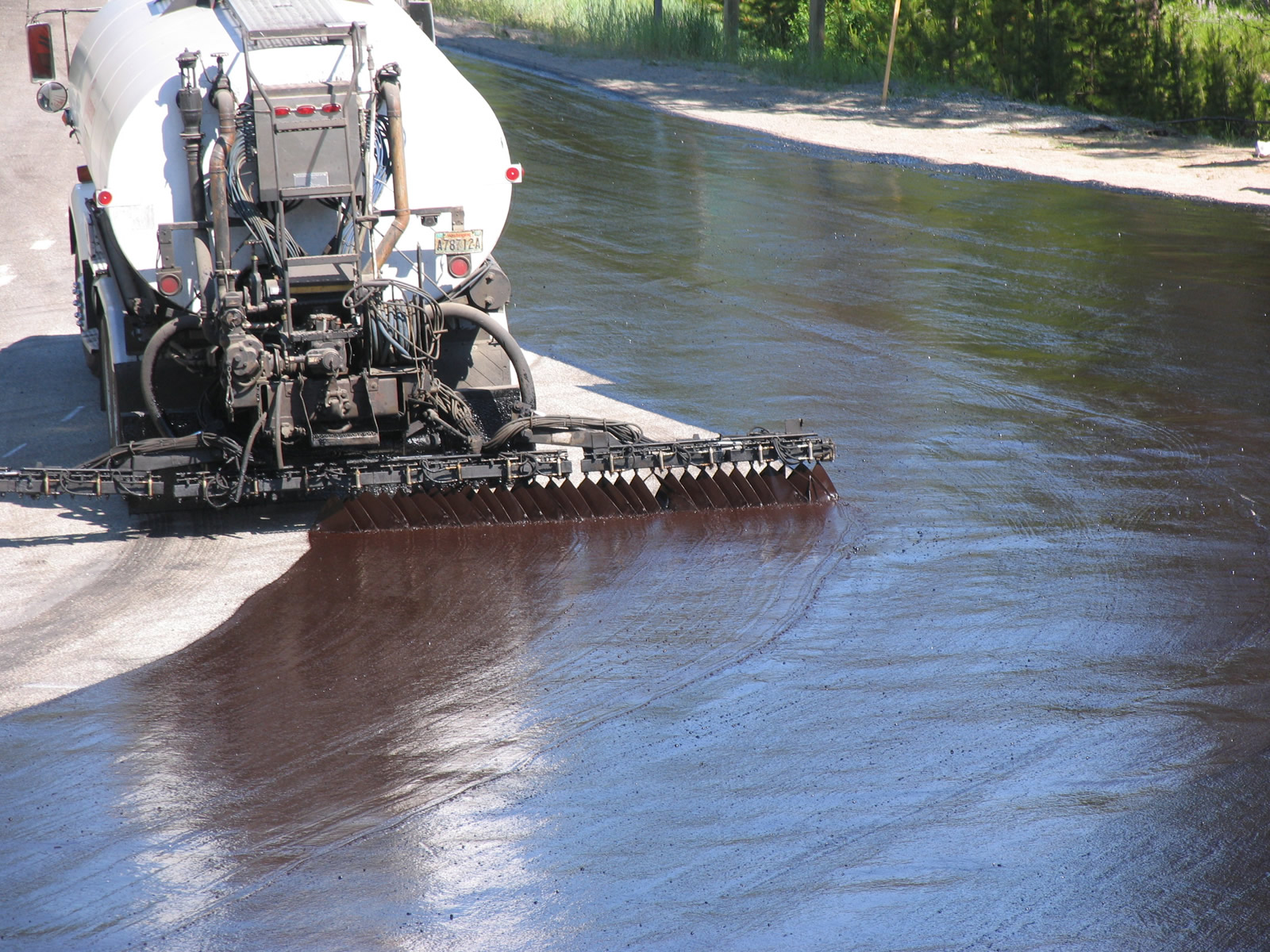 Freshly placed asphalt emulsion for a bituminous surface treatment; notice that the application rate is higher than that for a tack coat.
