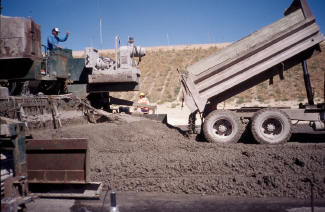 End dump truck discharging PCC in front of a paver.