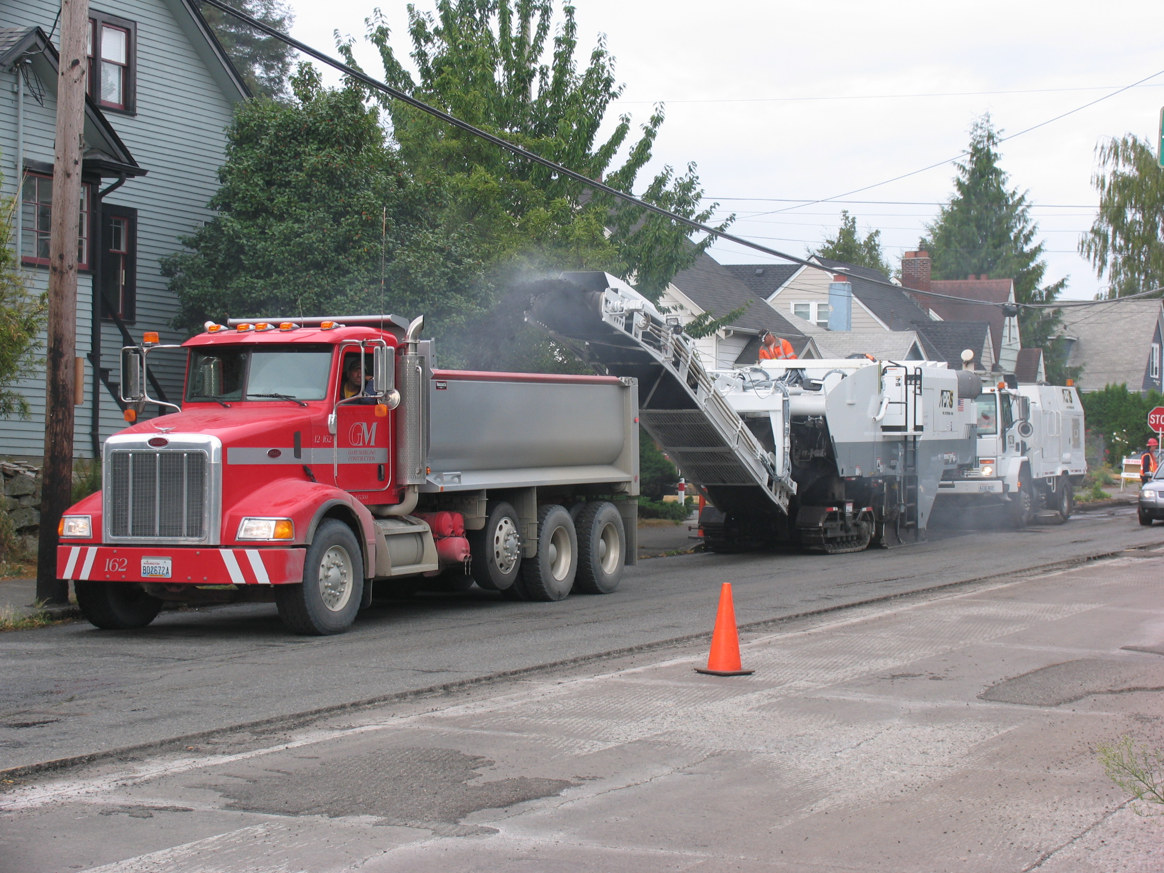End dump truck receiving milled pavement.