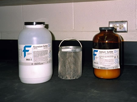 Aggregate basket surrounded by sulfate bottles.
