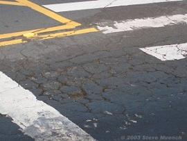 Severe alligator cracking near the stop line at a major arterial intersection.
