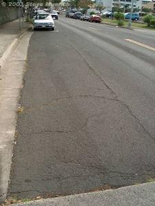 Block cracking in a parking lane. Parking lanes see little if any traffic, therefore the only likely distresses that will occur are raveling and block cracking. These cracks are probably too wide to be effectively crack sealed.