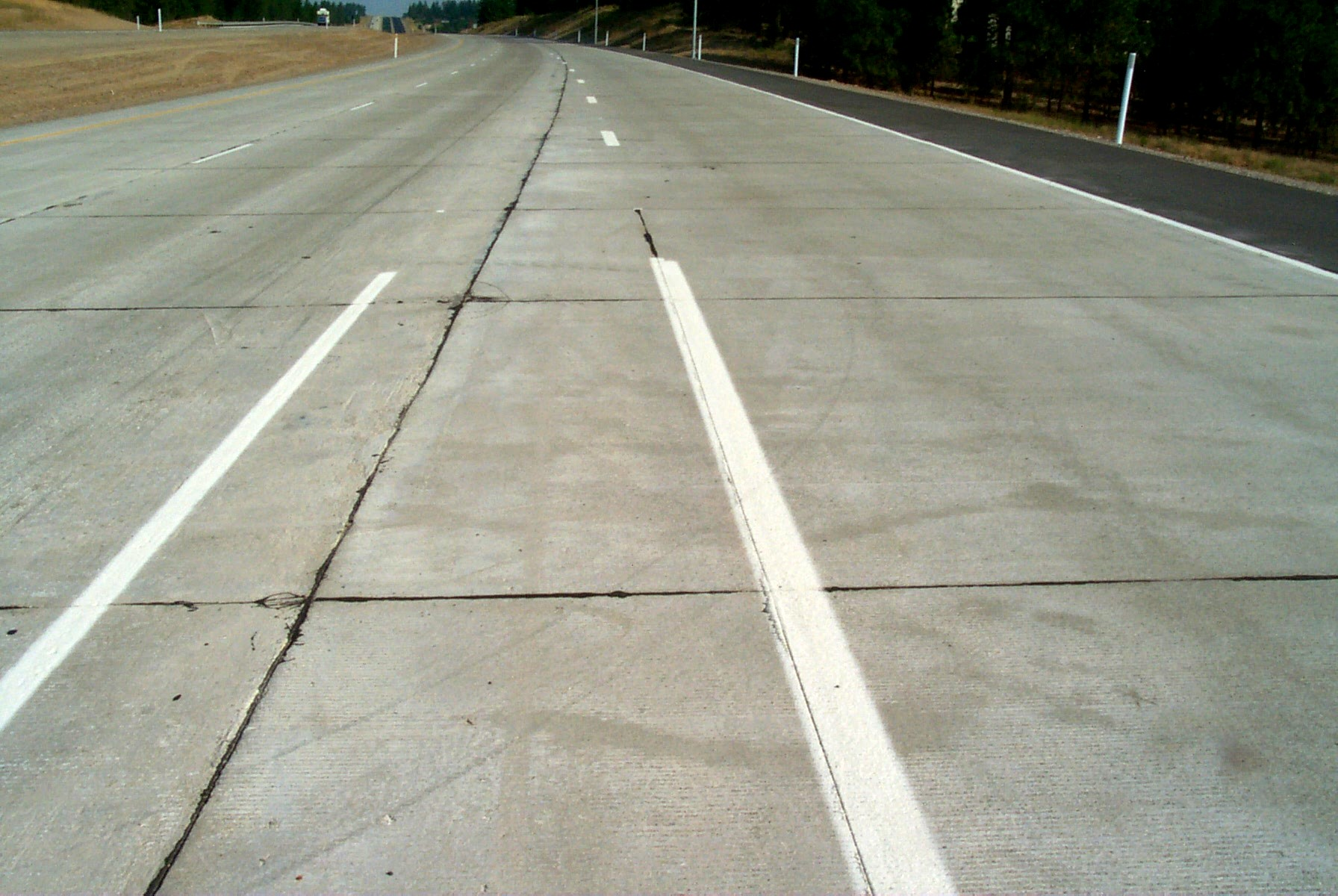 Joints sealed with hot-pour liquid sealant on a freeway on-ramp (normally, joints should coincide with lane divisions as they do near the horizon of this photograph)