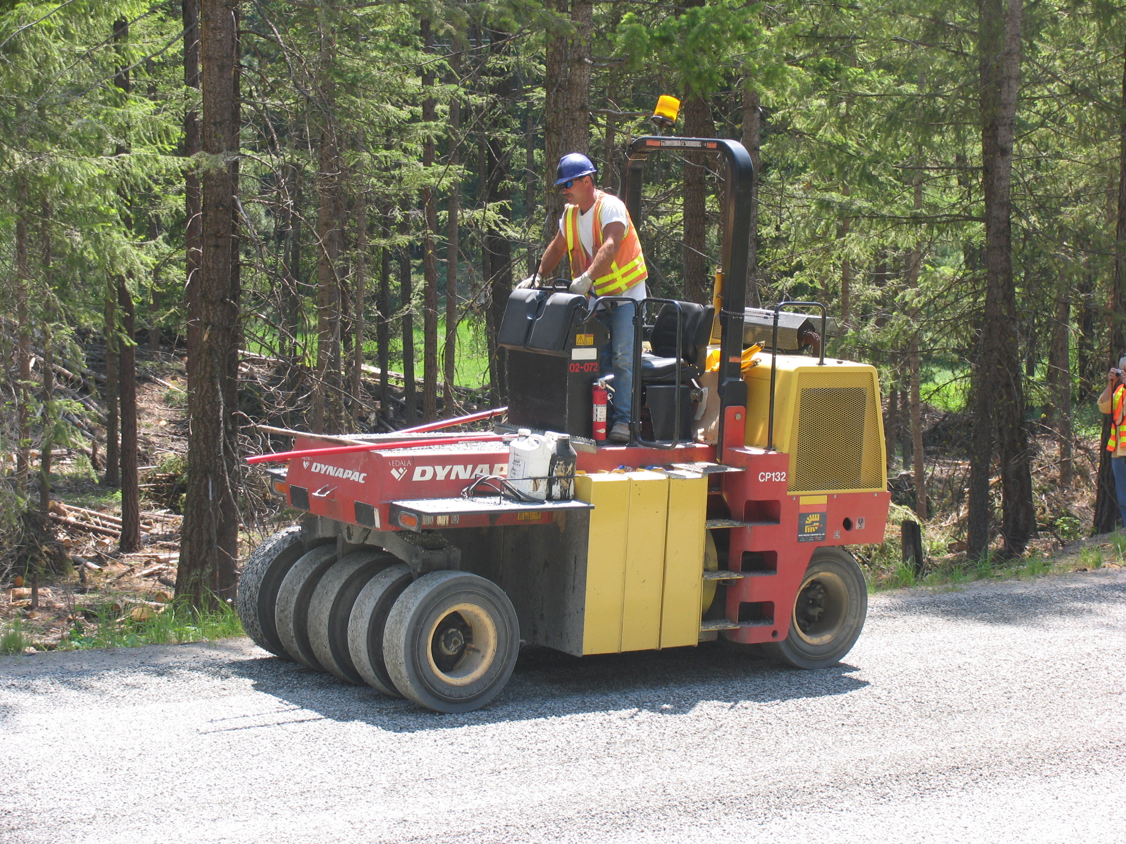 Embedding the aggregate into the asphalt using a pneumatic tire roller.