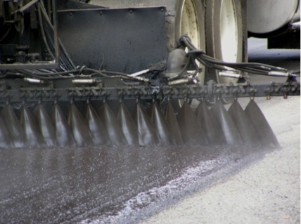 Close-up of asphalt emulsion being sprayed onto a prepared surface. The spray bar allows for consistent coverage of one lane-width at a time.