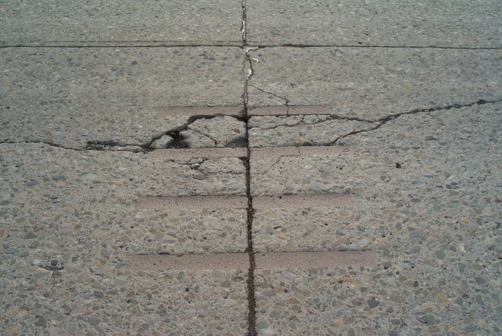 Failure of dowel bar slot placed over existing longitudinal crack.