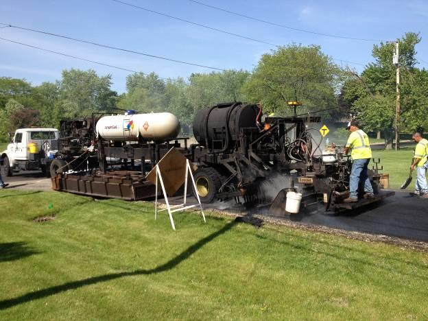 In the photo above, a surface recycling train places the rejuvenated asphalt mix in preparation for compaction and a subsequent wearing course, in this case a chip seal is to follow. (Photo courtesy of IPMA International Pavement Management Association)