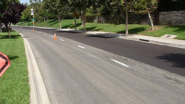 The example above depicts the sequence of pre milling to lower the insitu grade of the hot mixed asphalt section on the left, followed by the new CIR mat on the right, in preparation for a HMA wearing course. (Photo courtesy of IPMA International Pavement Management Association)