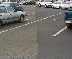 A parking lot shown with a fog seal (right) and without (left).