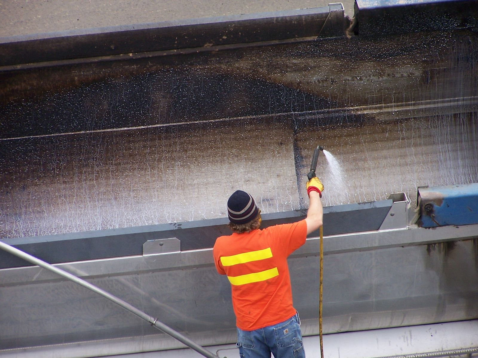 A worker applying a release agent to the bed of a truck before it is loaded with asphalt mix.