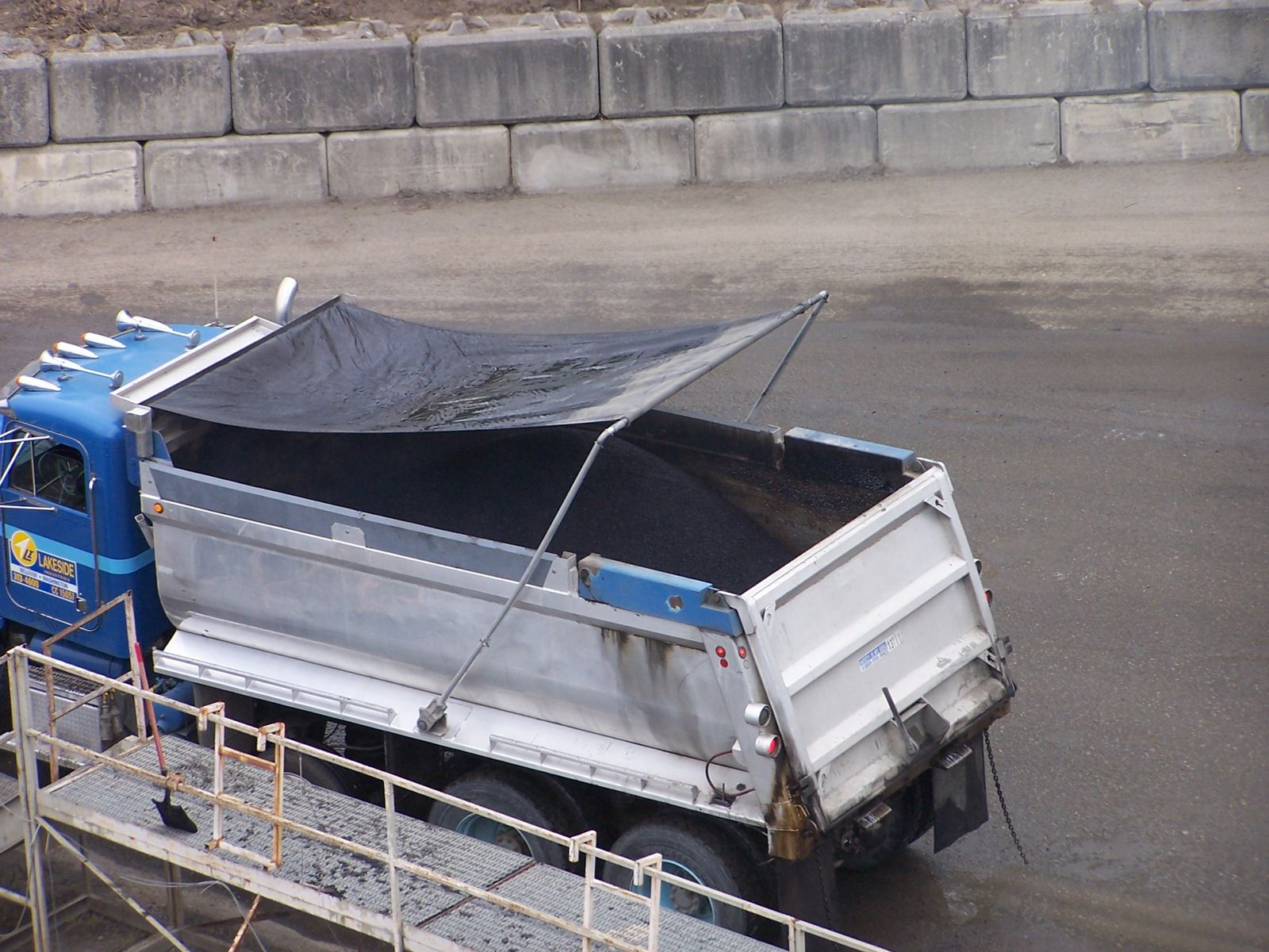 A load of asphalt mix being covered with a tarp.