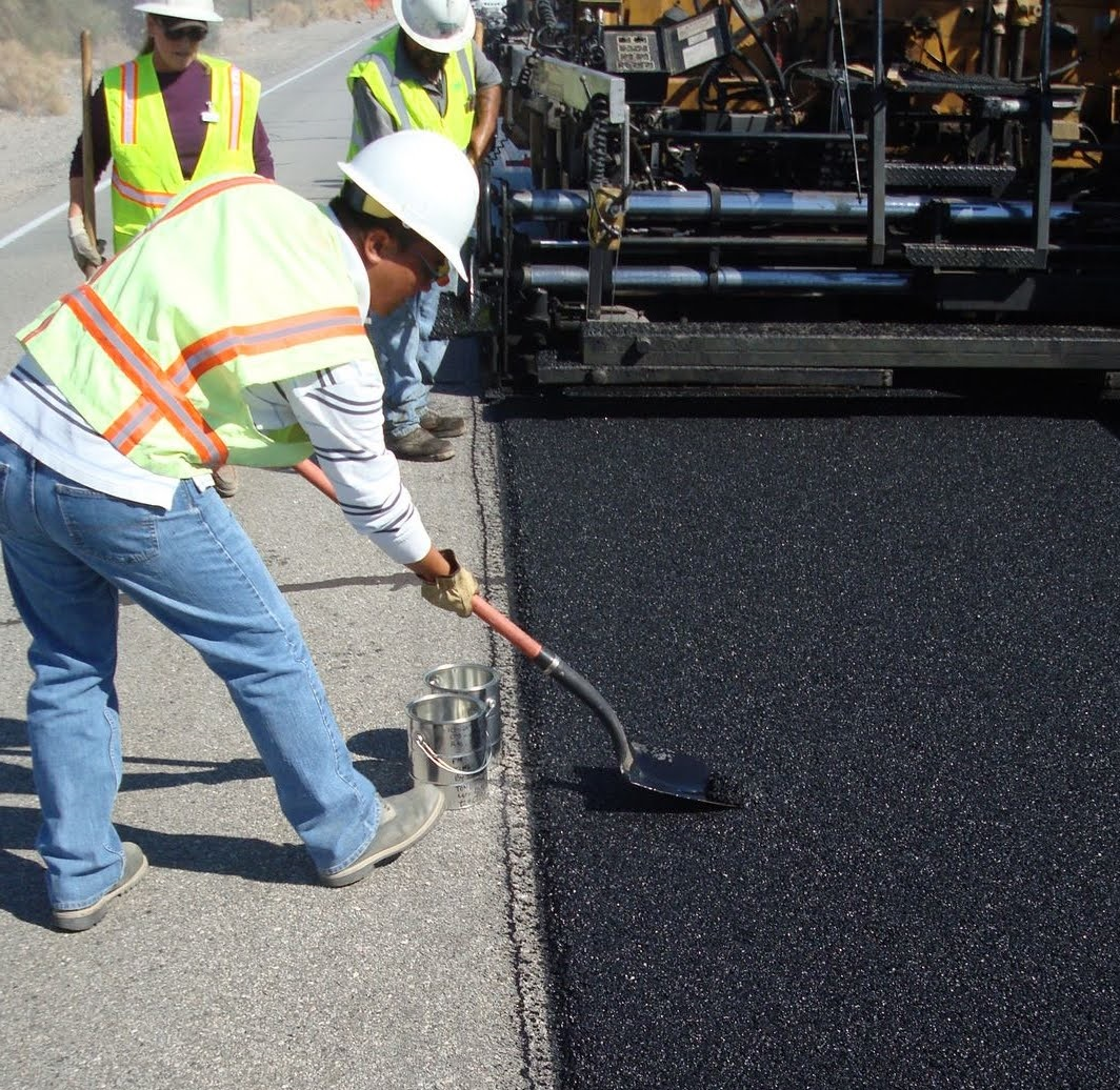 Inspector collecting asphalt samples behind the paver.